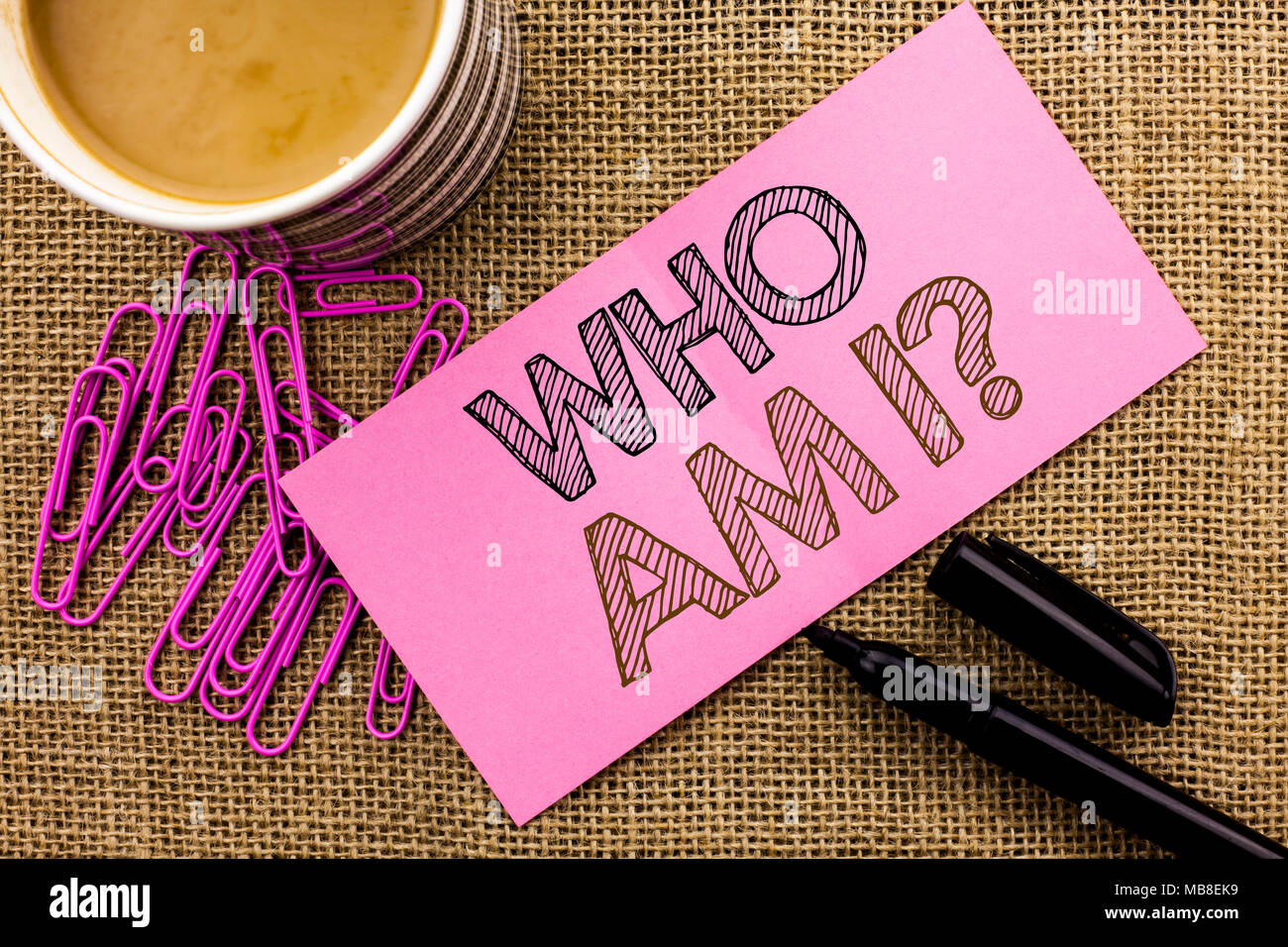 Handwriting text writing Who Am I Question. Concept meaning Question Asked Identity Thinking Doubt Psycology Mystery written on Pink Sticky Note Paper on the jute background Coffee Cup Pen Pins. - Stock Image
