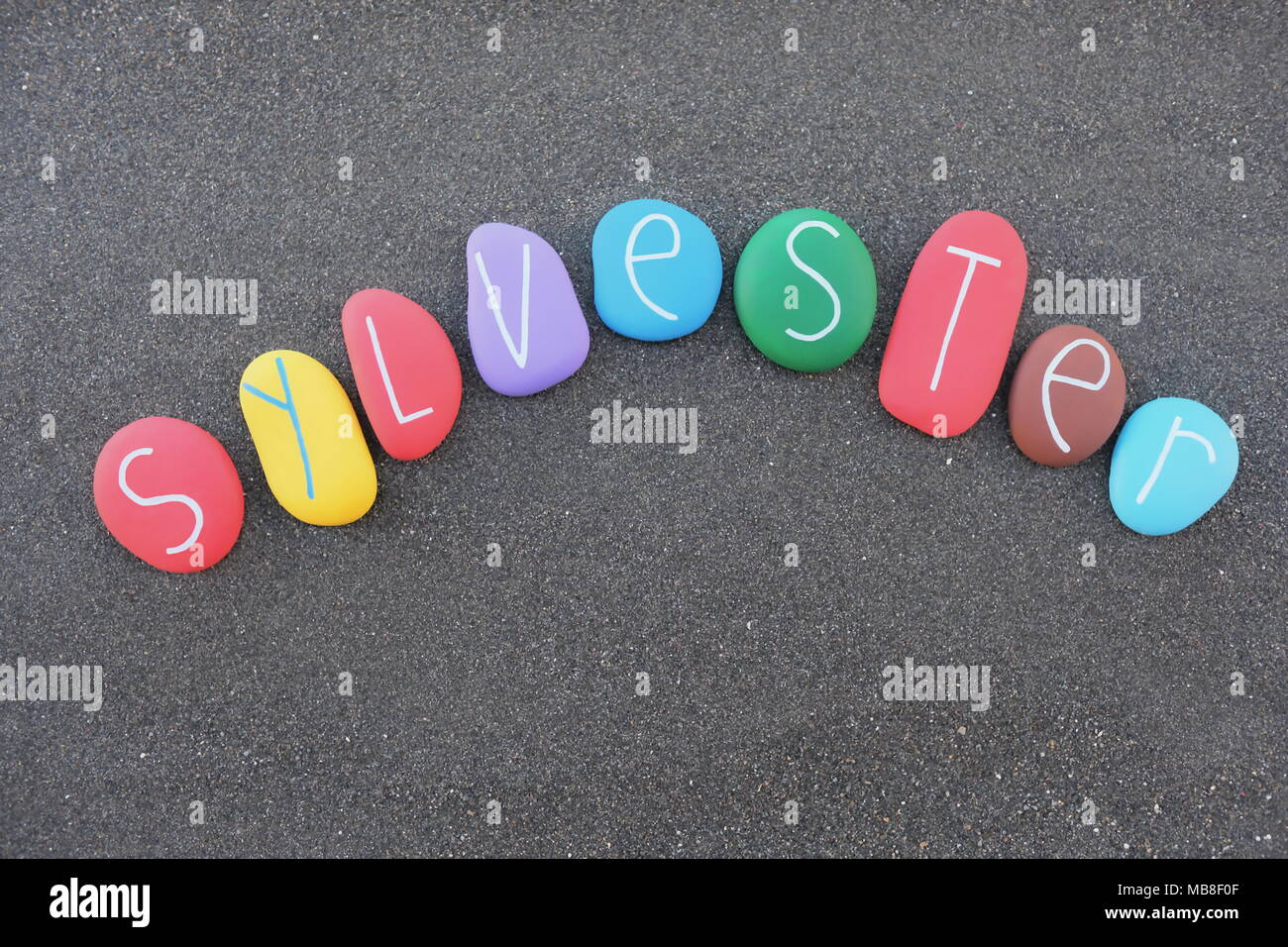 Sylvester, masculine name with multicolored stones over natural volcanic black sand Stock Photo