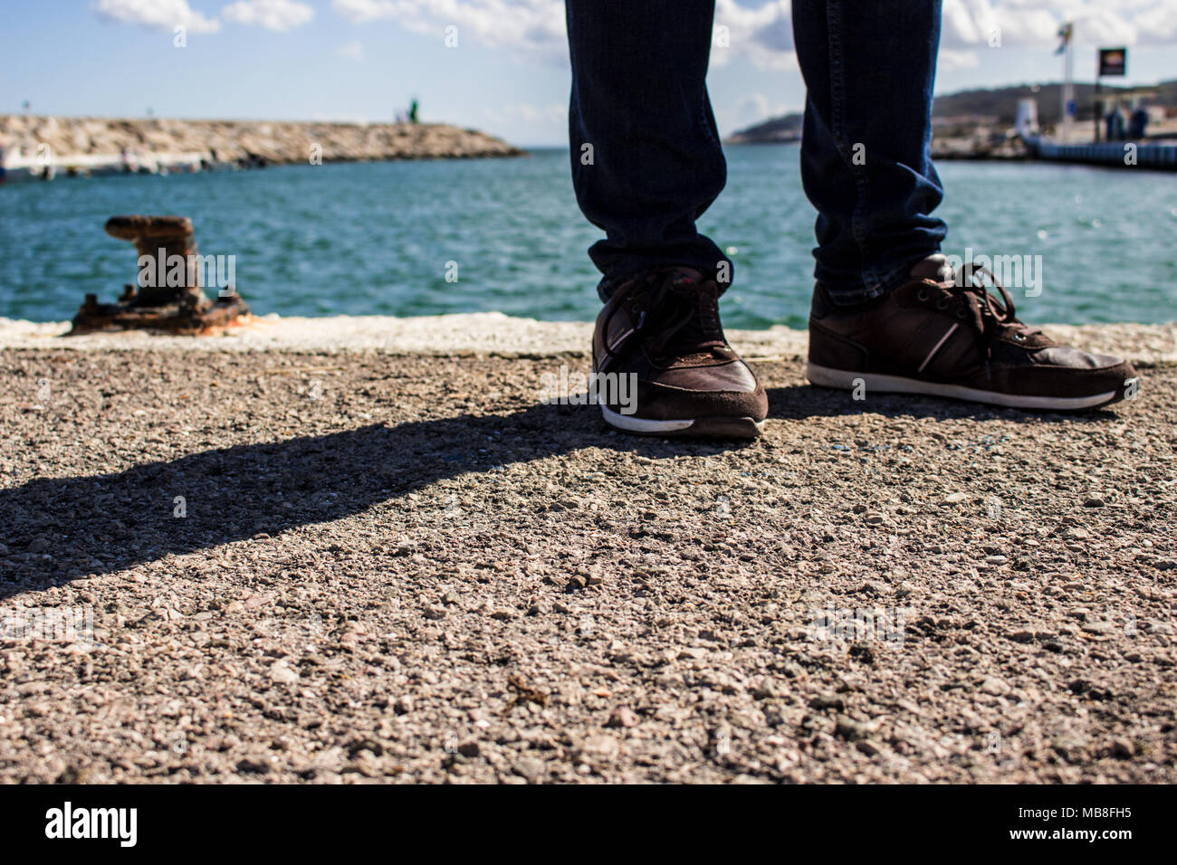 Shoes. A man in casual shoes on a pier near the sea. - Stock Image
