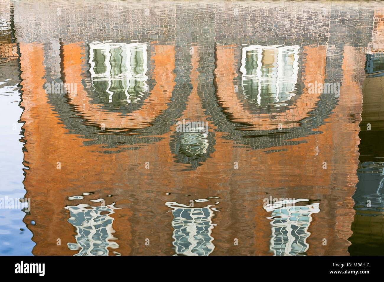 Abstract water reflections of an old red brick building in Worcester, UK - Stock Image