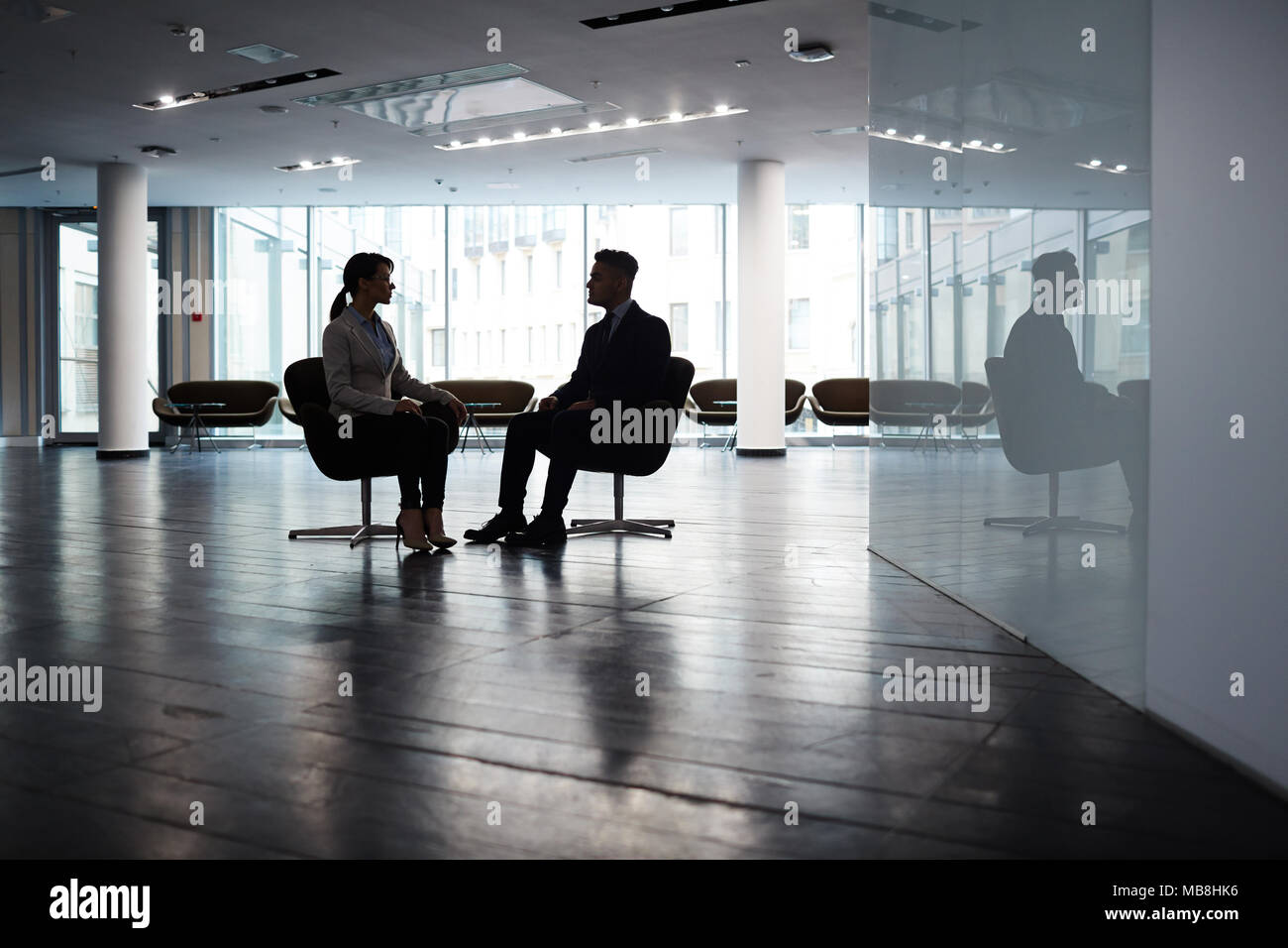 Confident young manager sitting opposite her male partner while brainstorming on joint project, interior of spacious dim office lobby on background - Stock Image