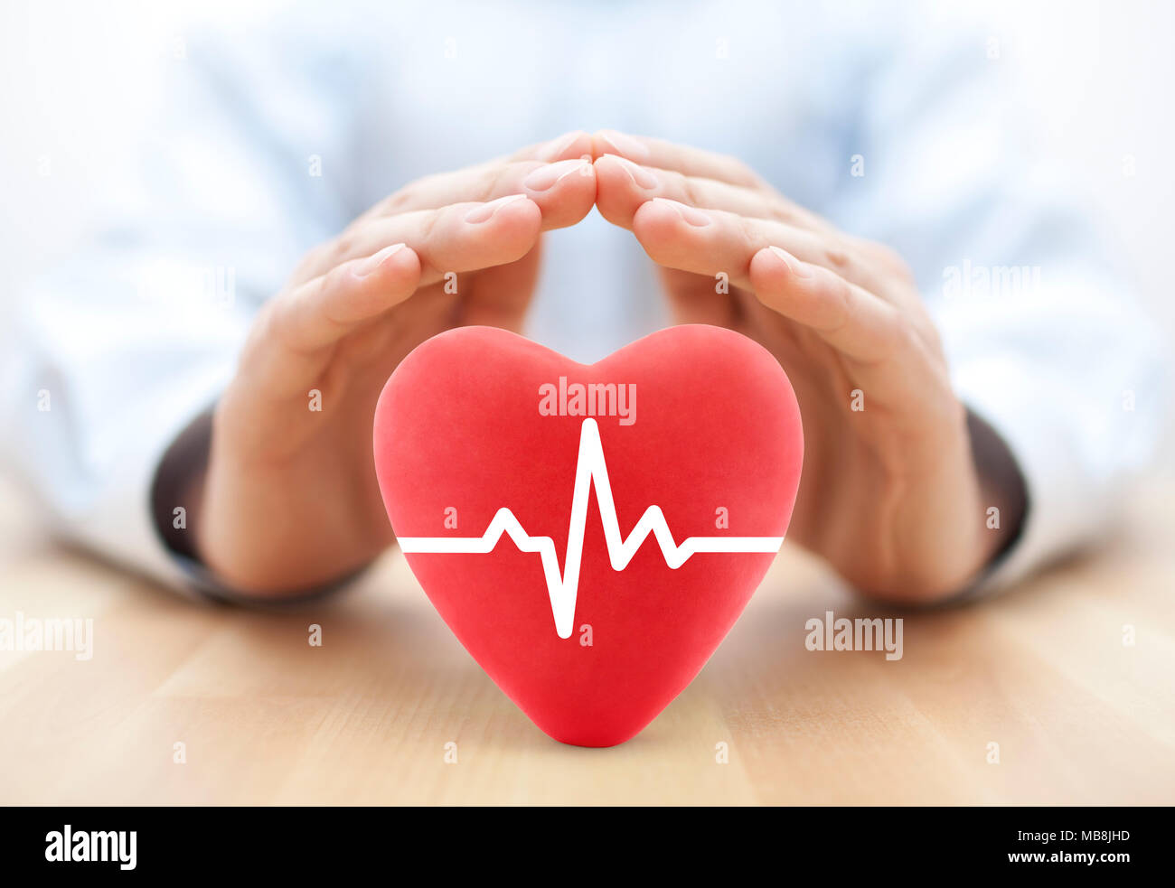 Heart pulse covered by hands. Health insurance concept - Stock Image