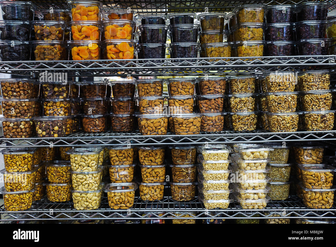 Pile of various dried fruit and nuts packaged in airtight transparent plastic containers for convenience and freshness, positioned on a metal rack Stock Photo