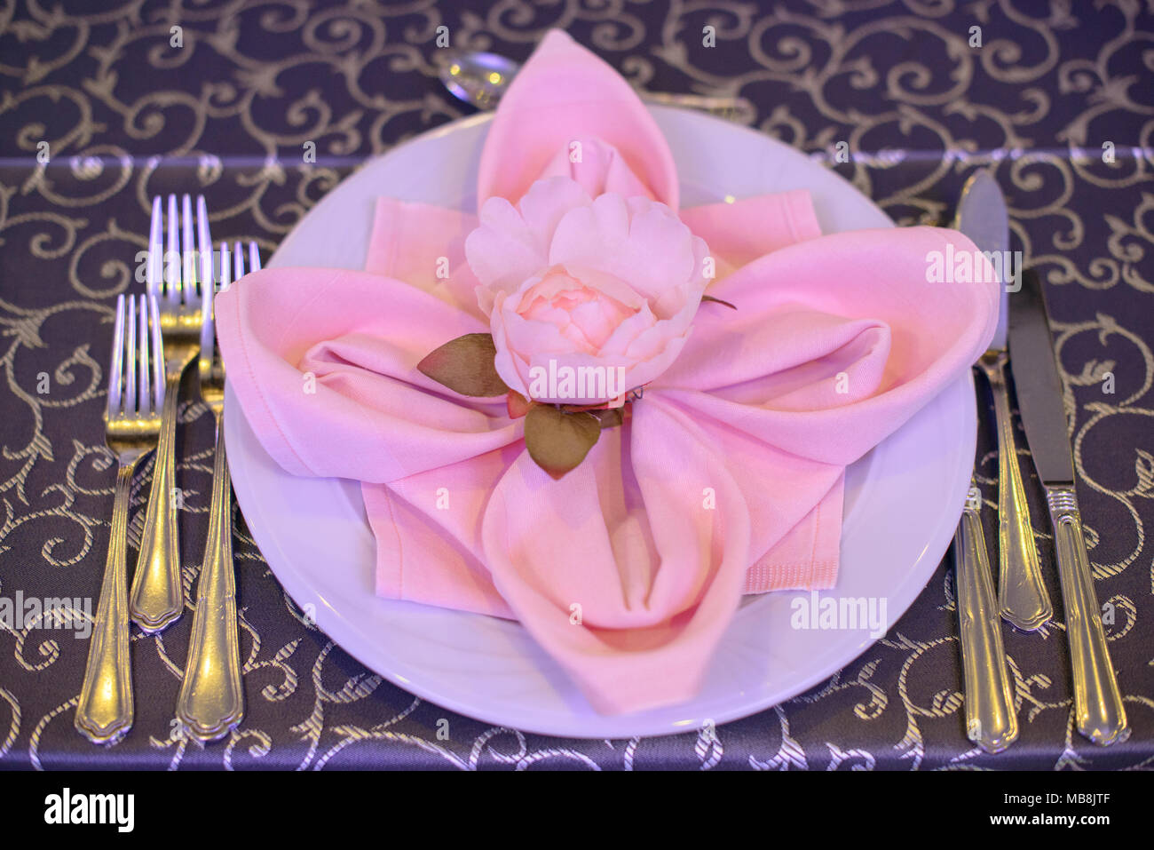 Formal table setting with silverware placed in the order of use and elegantly wrapped napkin in the shape of a flower on top of white china & Formal table setting with silverware placed in the order of use and ...