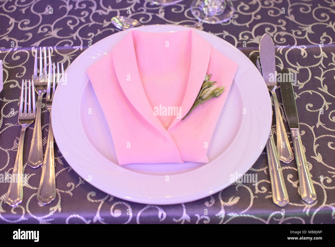 Formal table setting with silverware placed in the order of use and elegantly wrapped napkin in the shape of a jacket on top of white china & Formal table setting with silverware placed in the order of use and ...