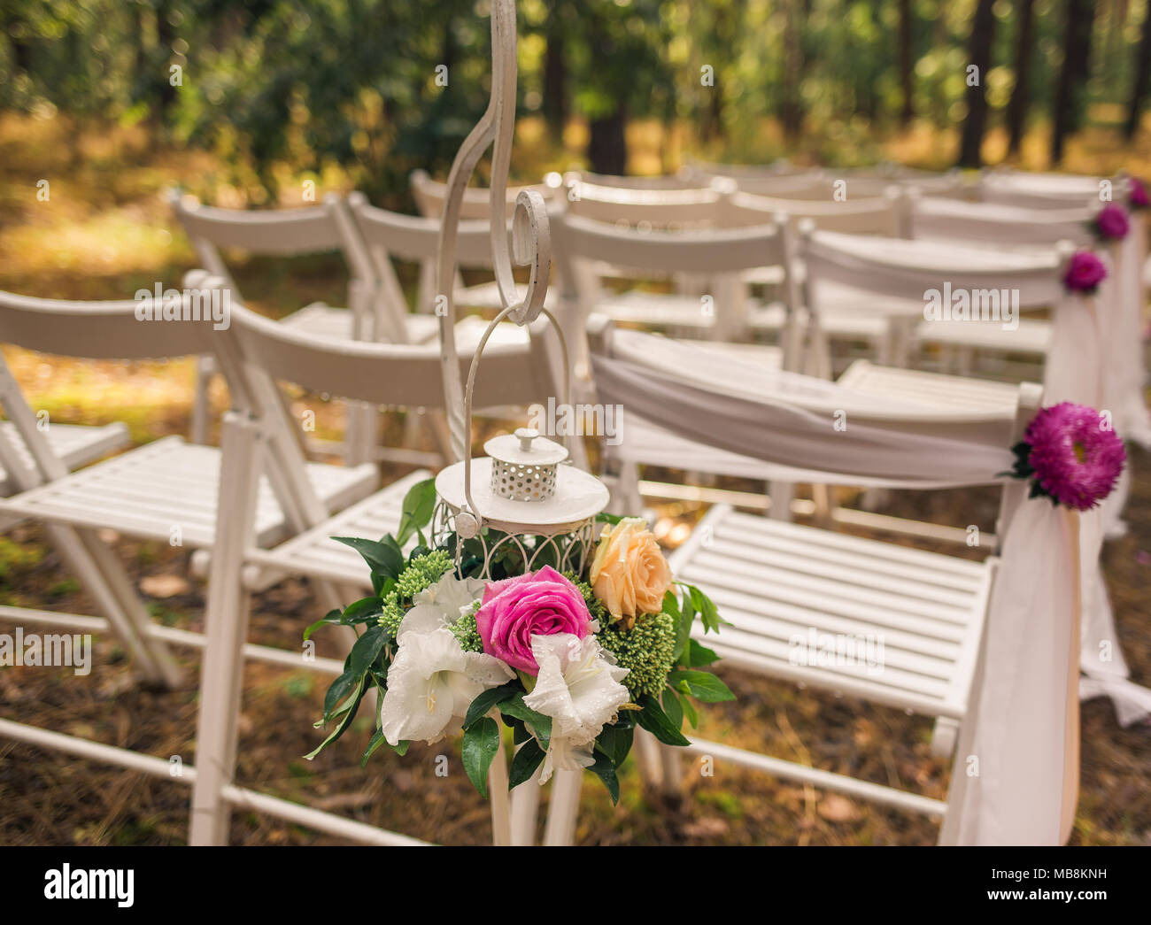 Floral elegant elements of wedding decorations. Settings for romantic wedding ceremony outside in sunny forest. White wooden empty chairs decorated wi Stock Photo