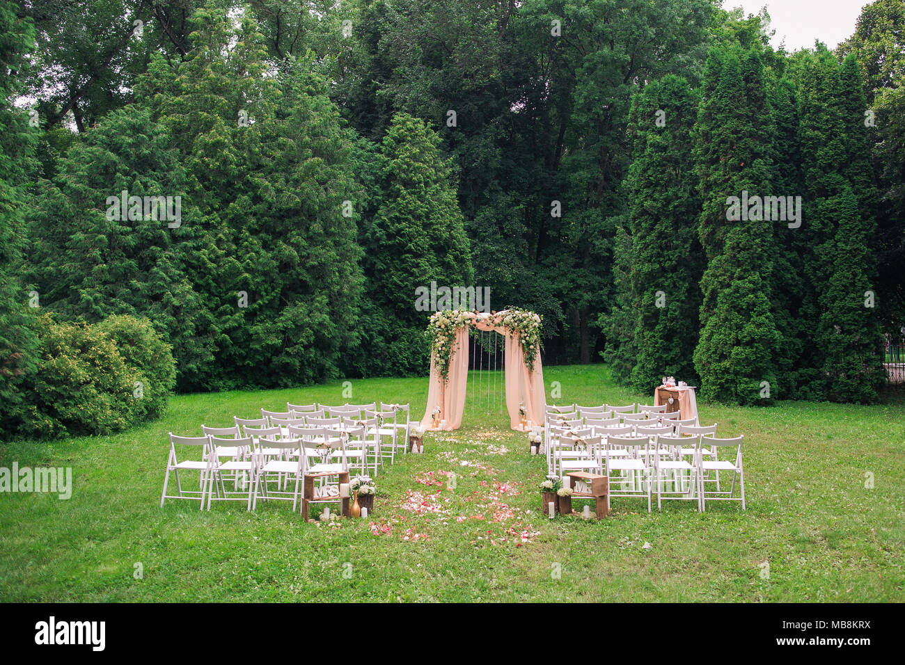Beautiful place made with wooden square and floral roses decorations for outside wedding ceremony in green park. Rows of many empty wooden chairs read Stock Photo
