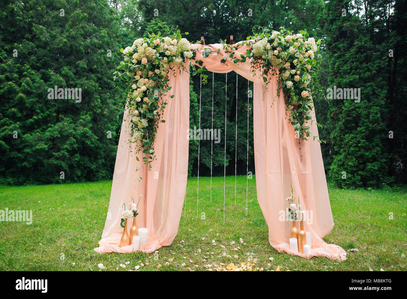 Beautiful place made with wooden square and floral roses decorations for outside wedding ceremony in green park. Wedding settings at scenic place. Hor Stock Photo
