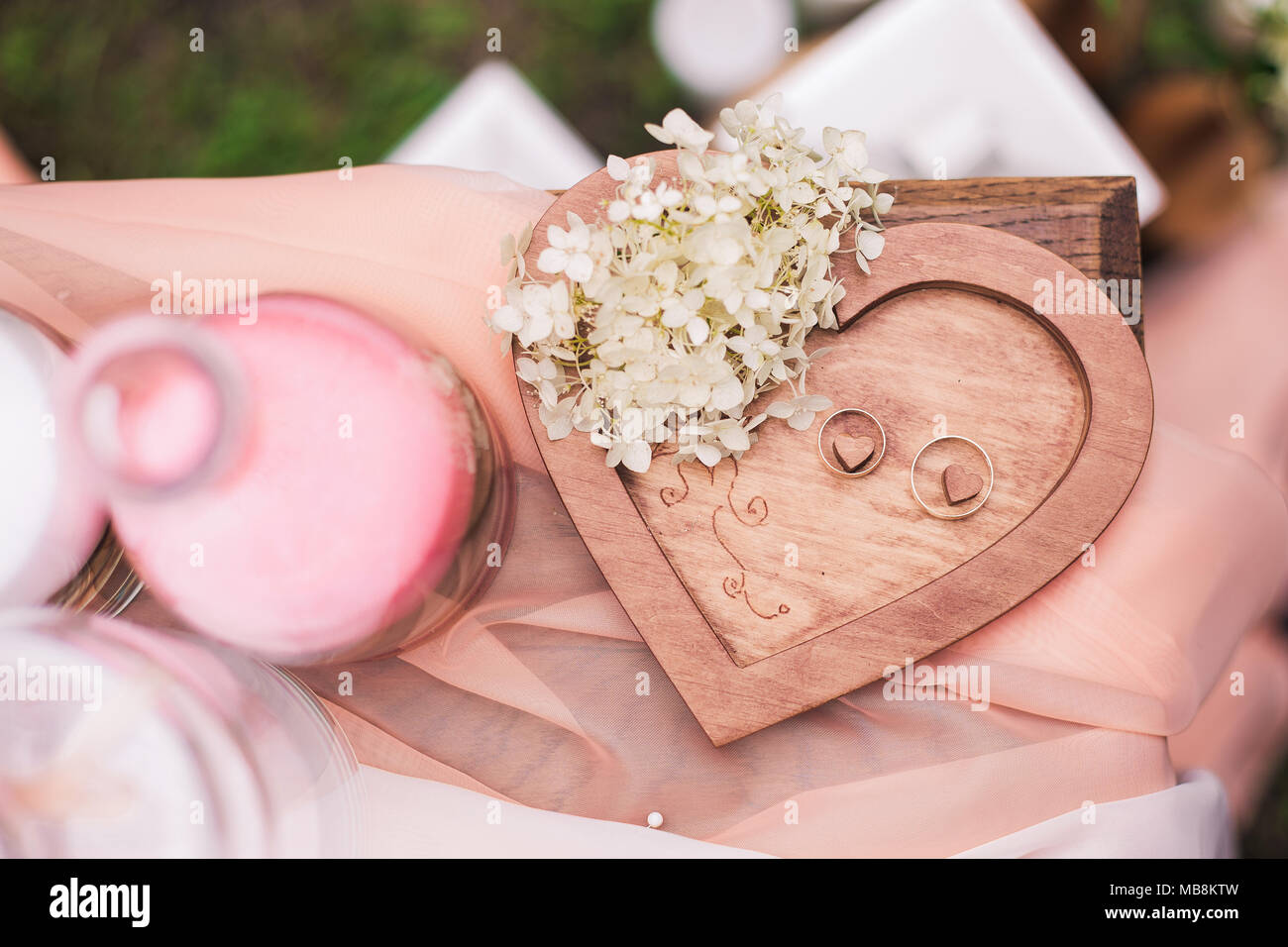 Closeup top view of two golden wedding rings on wooden heart ...