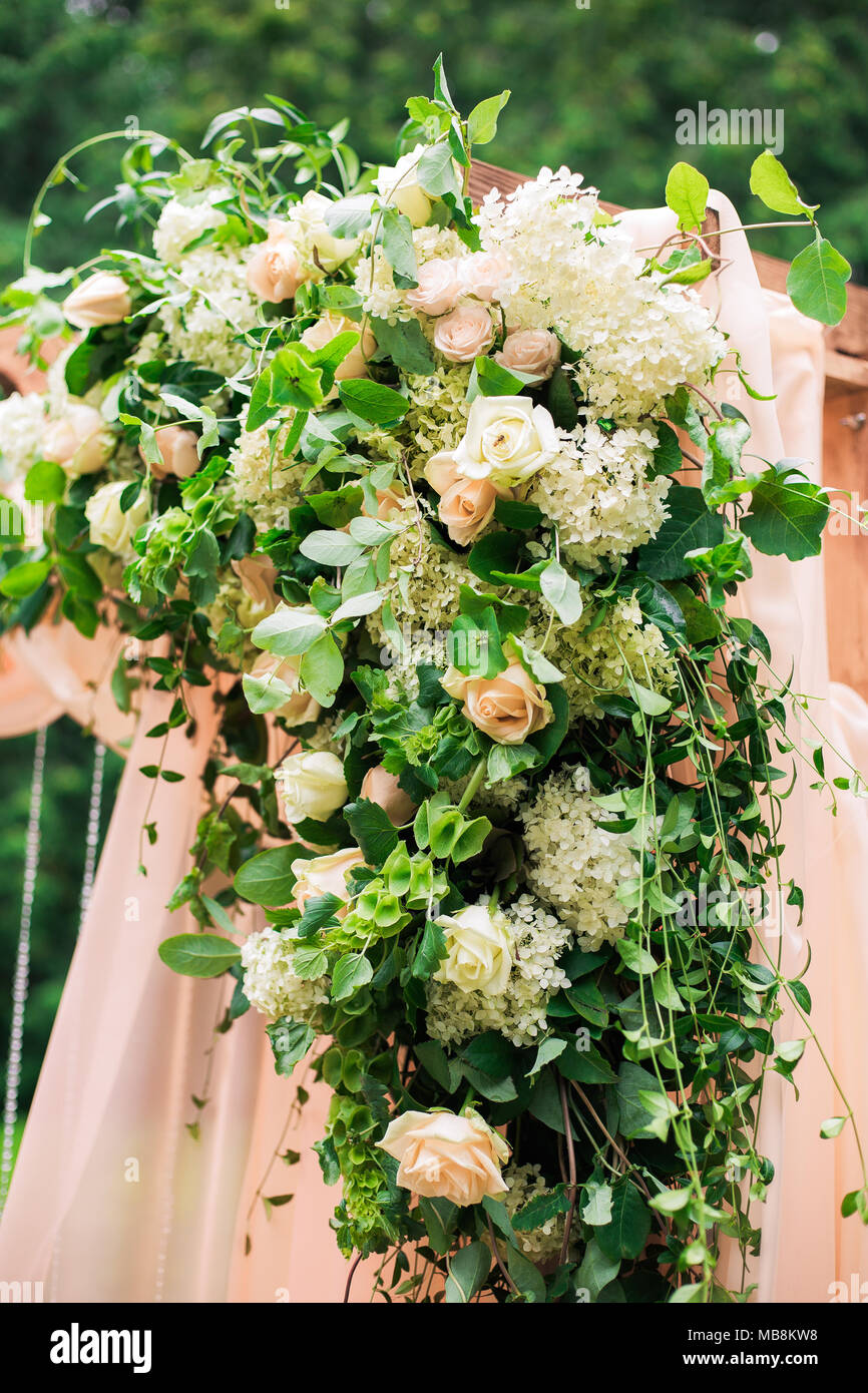 Beautiful place made with wooden square and floral roses decorations for outside wedding ceremony in green park. Wedding settings at scenic place. Ver - Stock Image