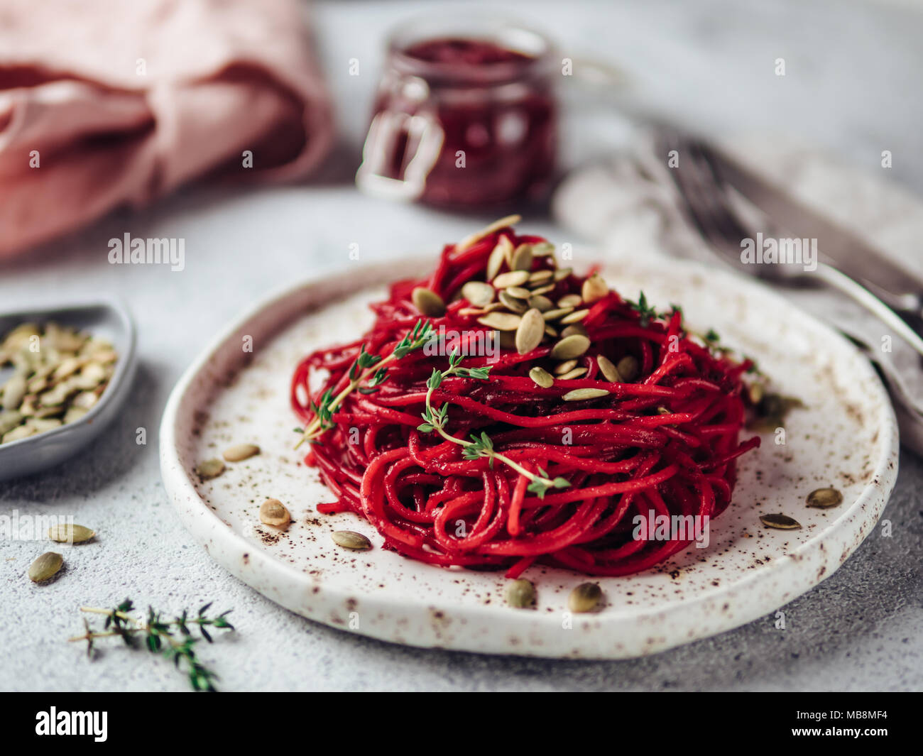 Roasted beetroot and thyme spaghetti with pumpkin seed in craft plate on gray cement background. Ideas and recipes for healthy vegan vegetarian dinner. Selective focus. - Stock Image
