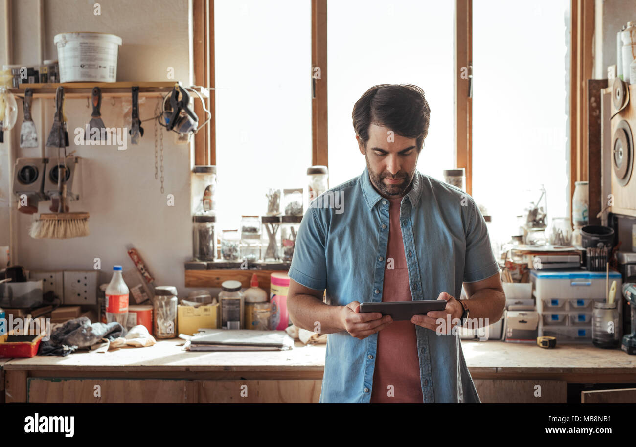 Woodworker working online with a tablet in his workshop Stock Photo