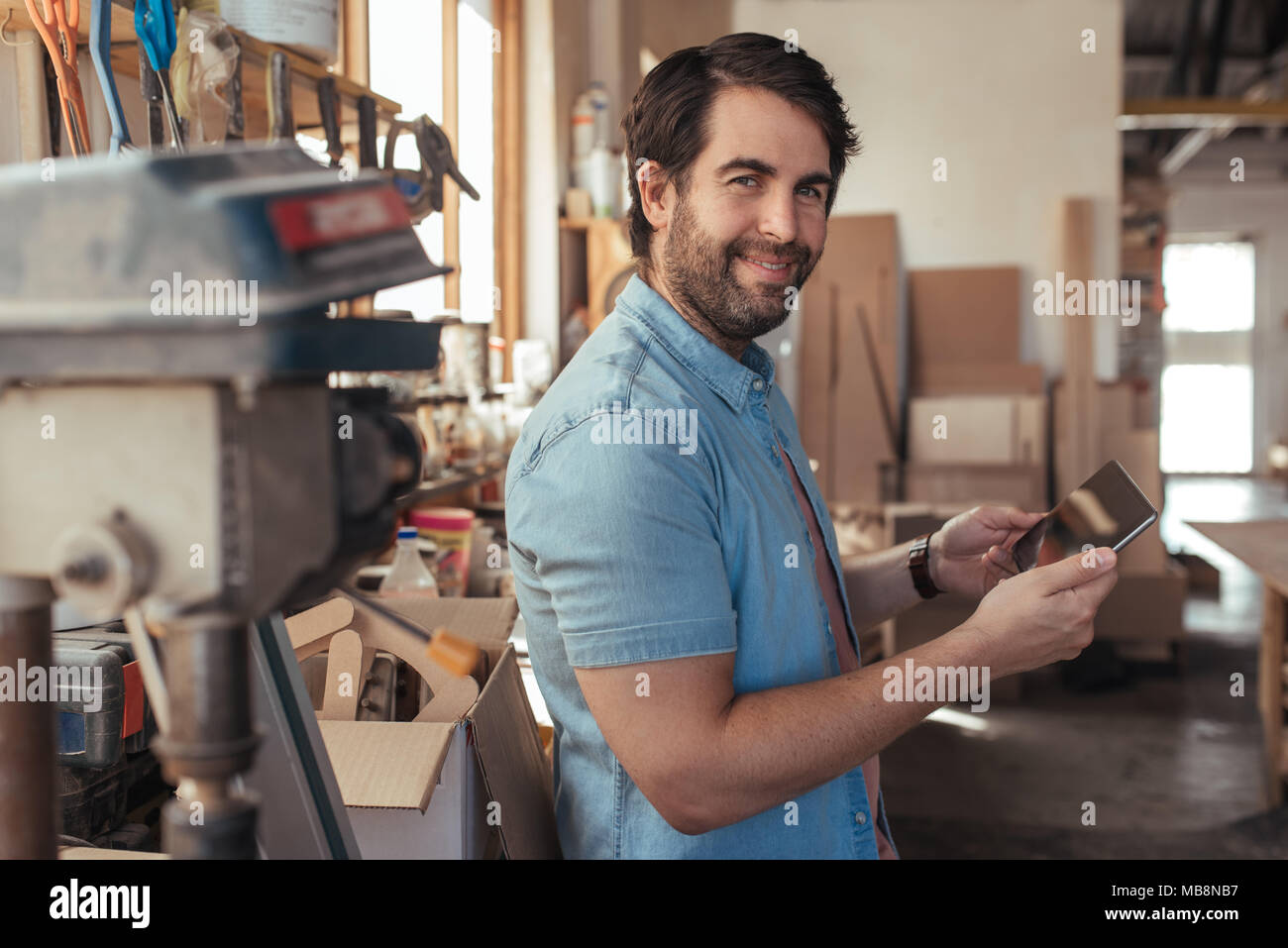 Smiling artisan using a tablet in his carpentry workshop - Stock Image