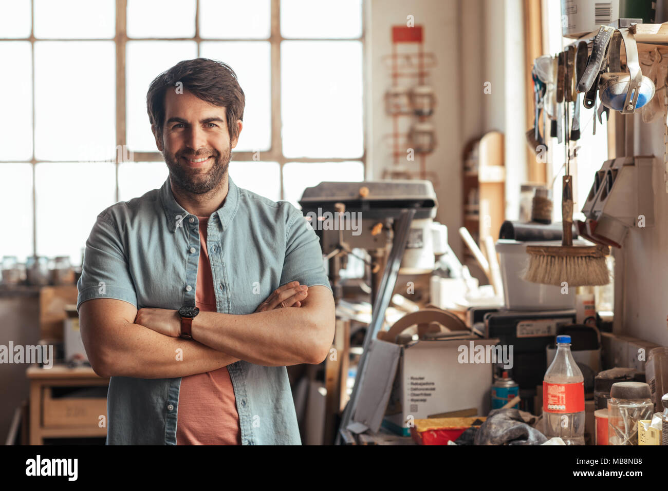 Smiling young woodworker standing by a bench in his workshop - Stock Image