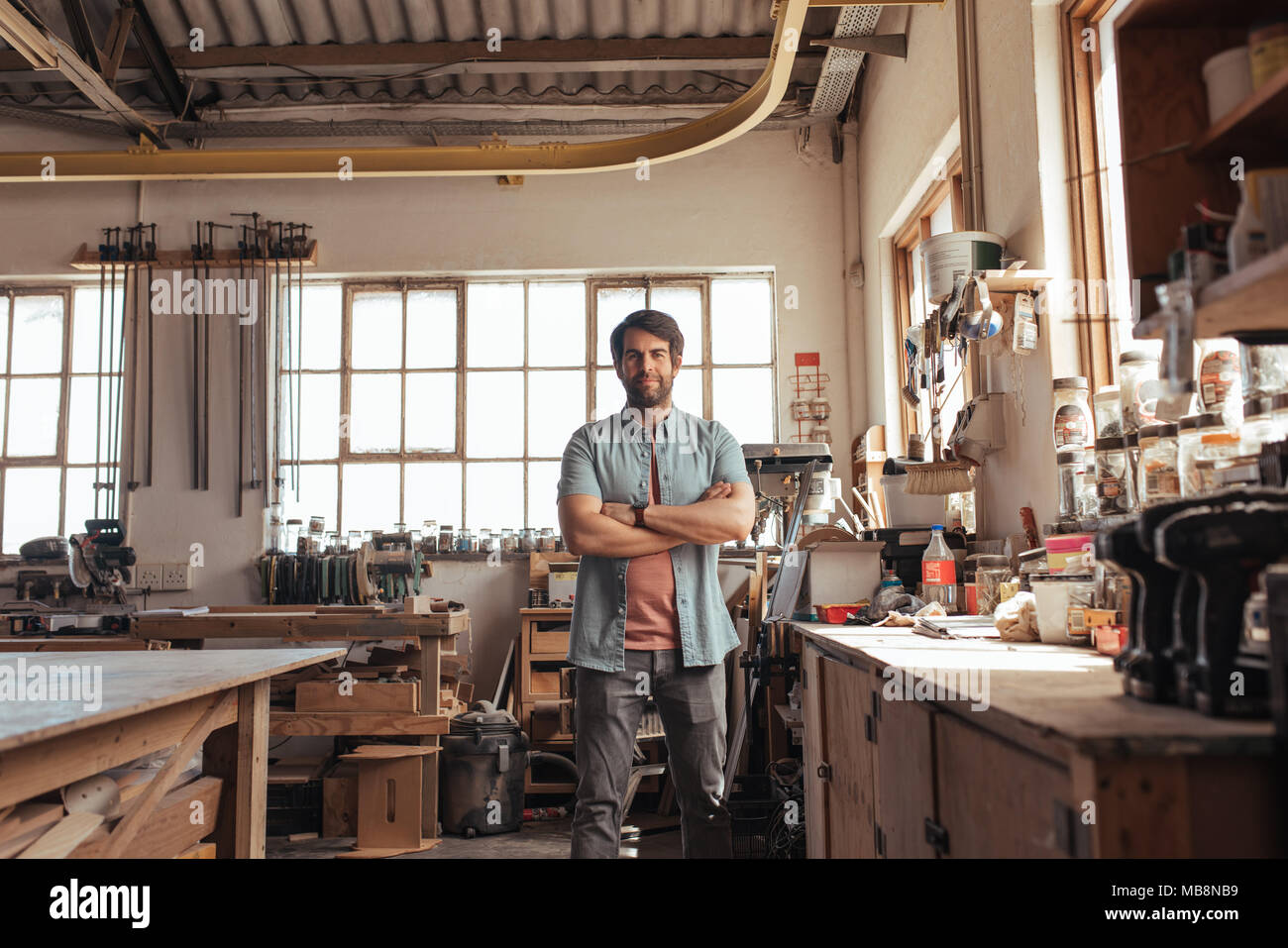 Confident young woodworker standing in his workshop full of tools - Stock Image