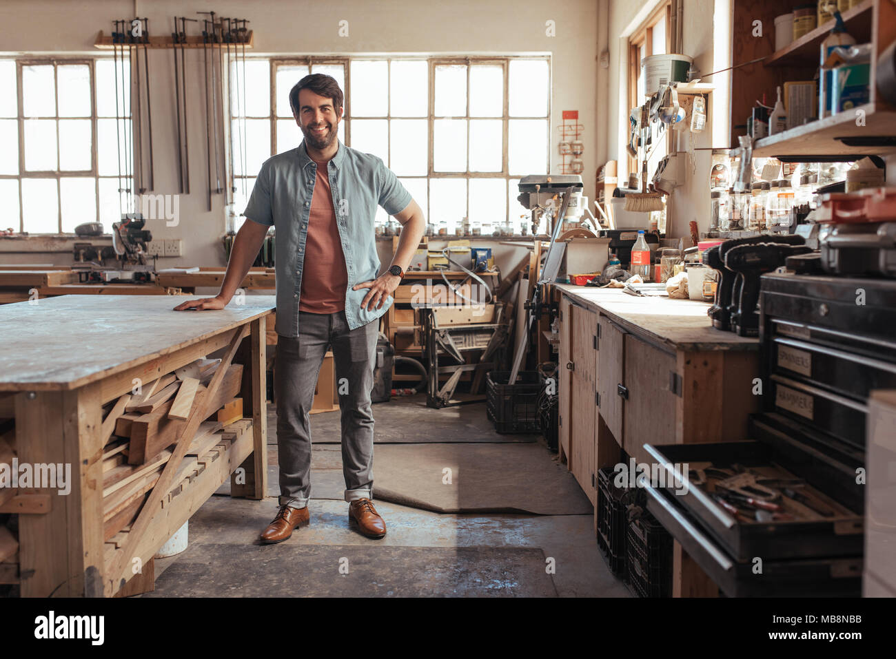 Smiling young woodworker standing by a table in his workshop - Stock Image