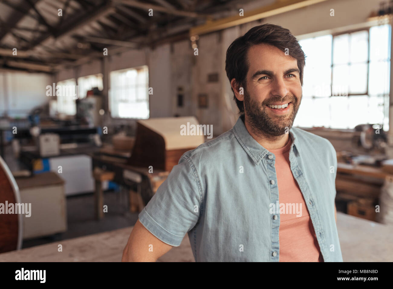 Smiling woodworker leaning on a table in his woodworking studio - Stock Image