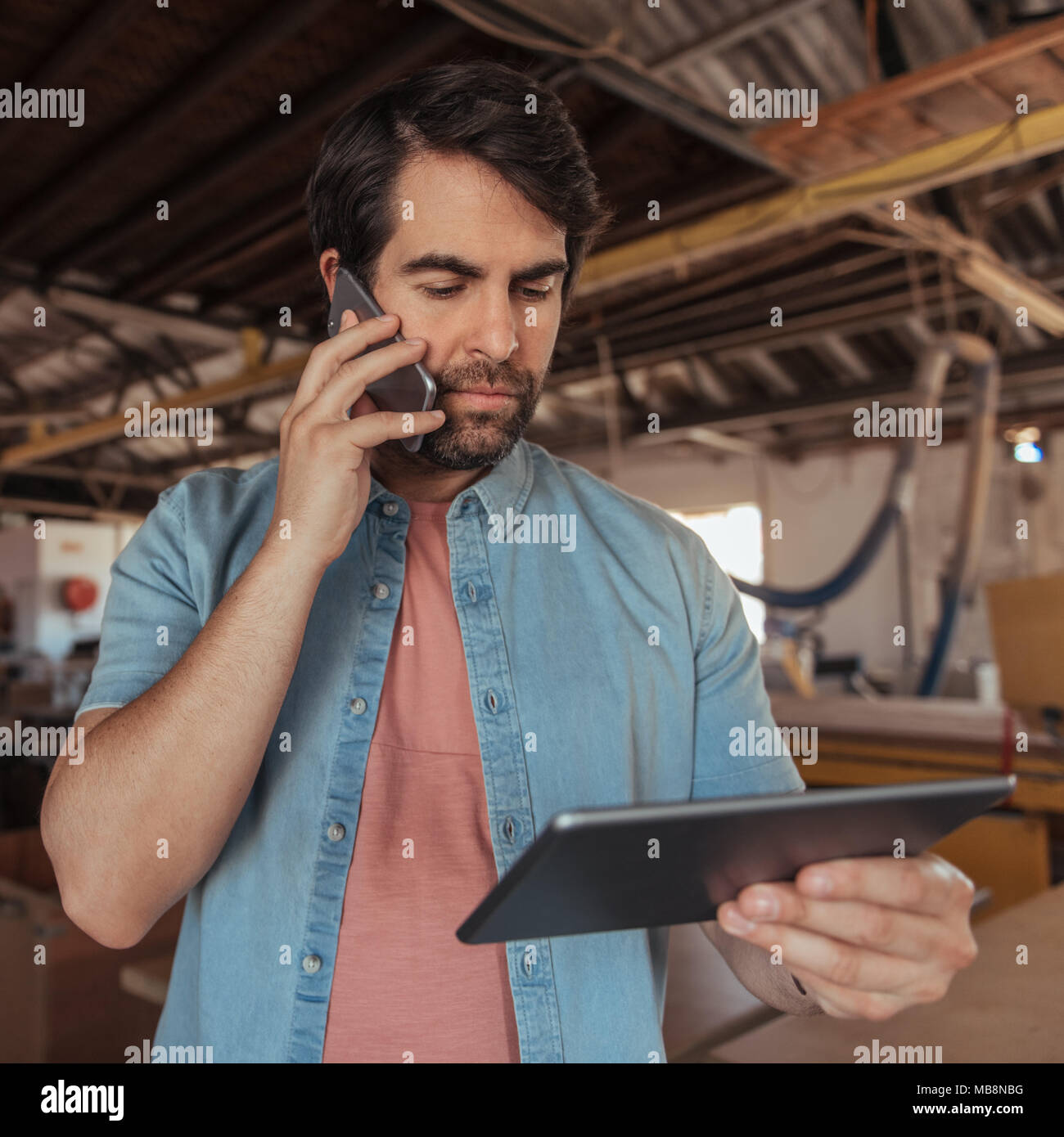 Young woodworker using a phone and tablet in his workshop - Stock Image