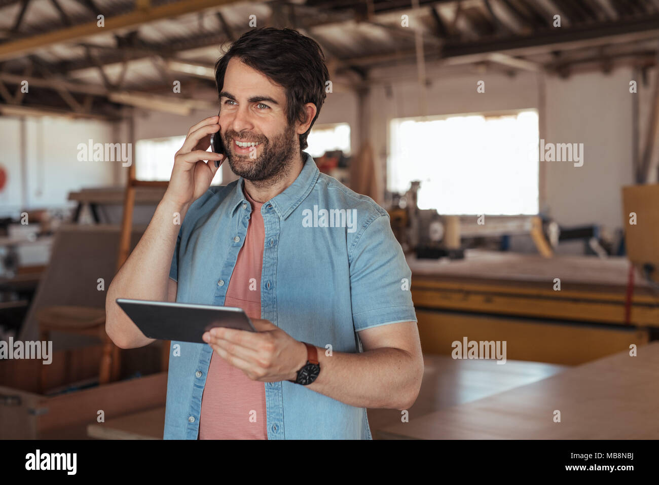 Smiling woodworker talking on his cellphone and using a tablet - Stock Image