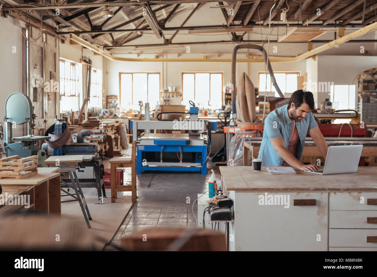 Young craftsman working on a laptop in his woodworking studio - Stock Image
