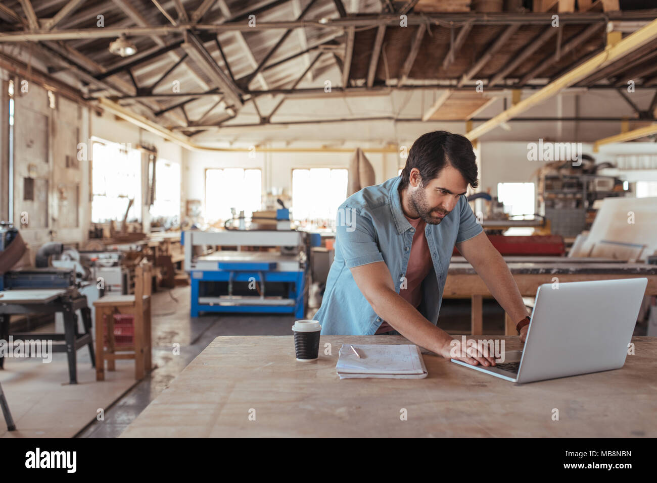 Young woodworker using a laptop in his workshop - Stock Image