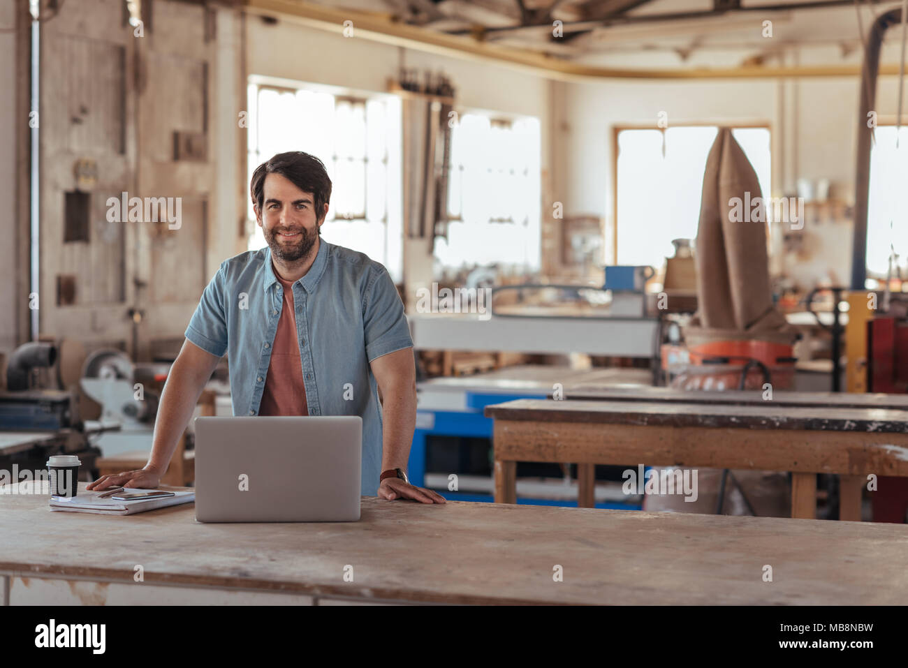 Smiling woodworker creating designs on a laptop in his workshop - Stock Image
