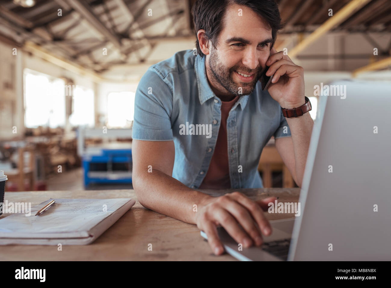 Woodworker discussing designs over the phone and using a laptop - Stock Image