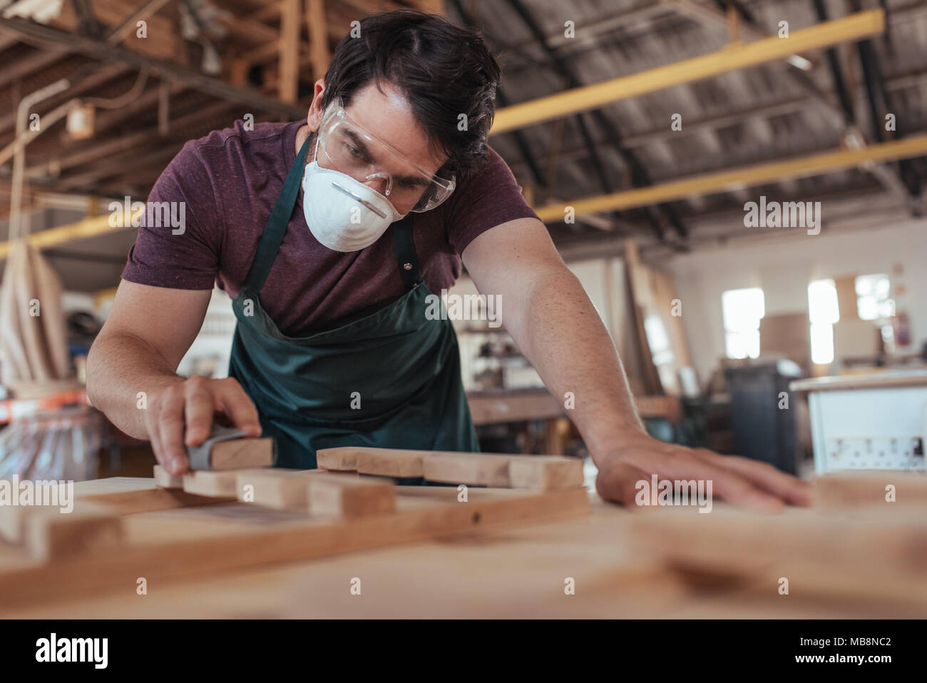 Young craftsman skillfully sanding wood in his large workshop - Stock Image
