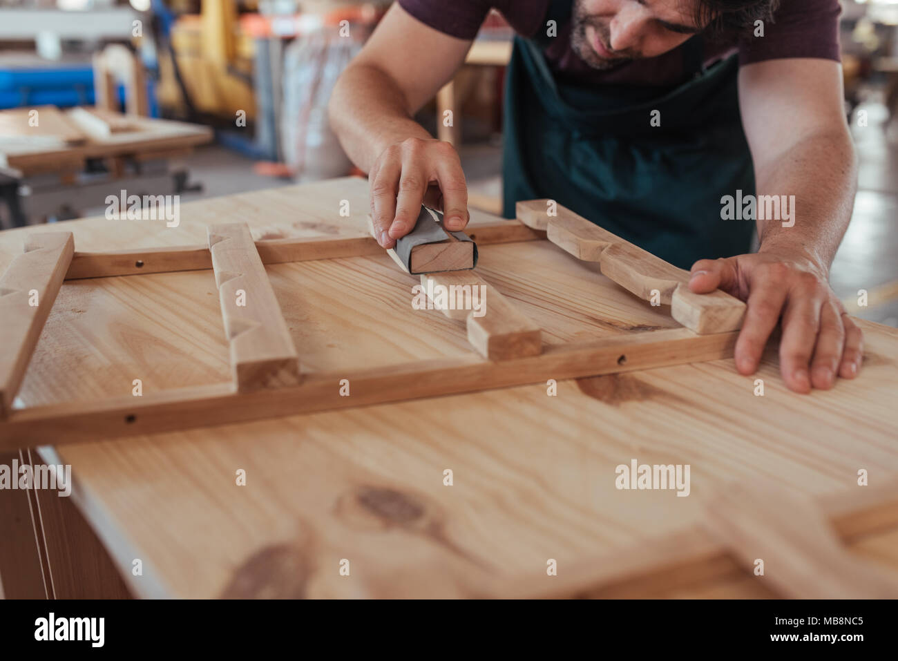 Craftsman skillfully sanding a piece of wood in his workshop - Stock Image