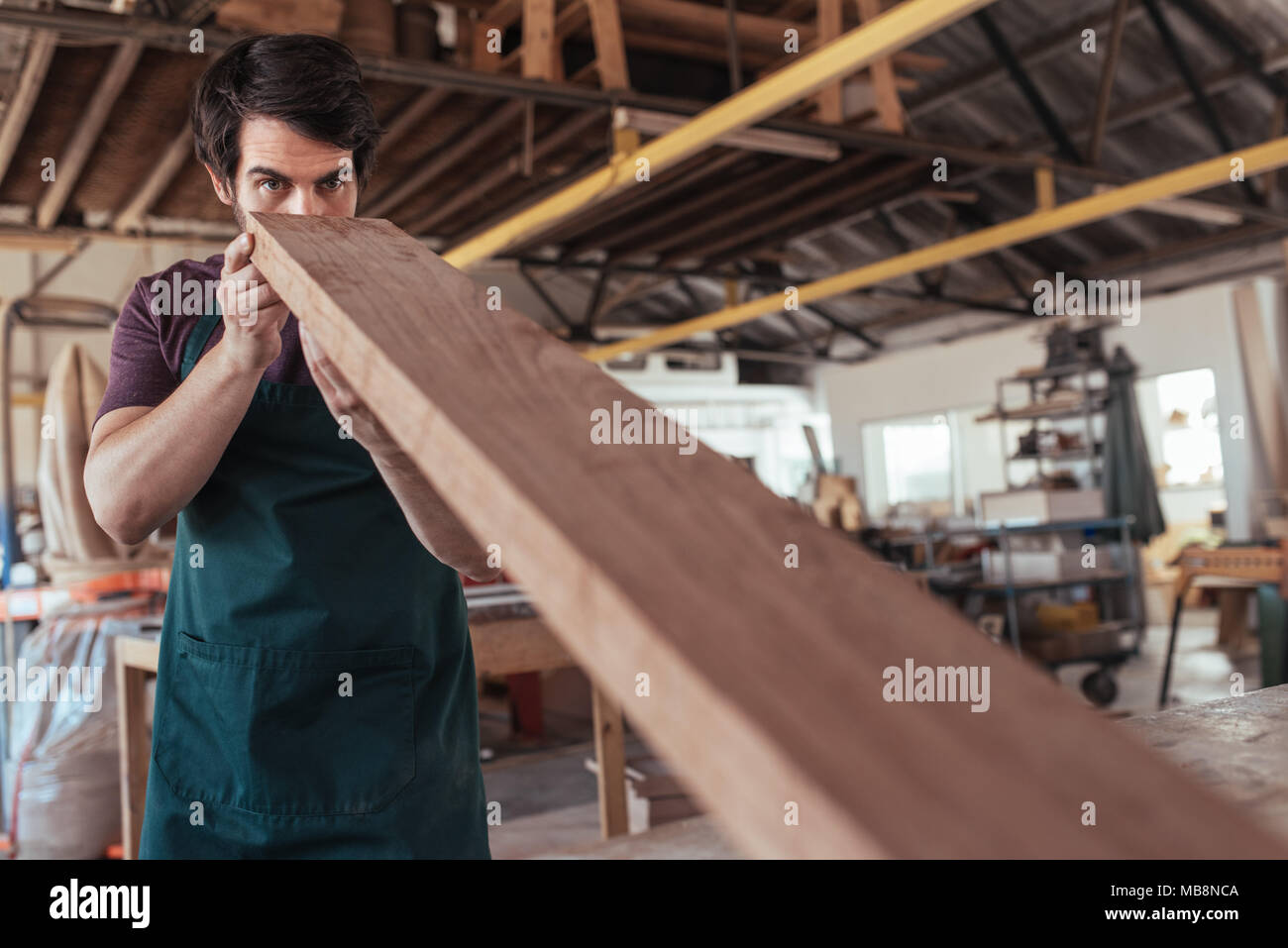 Woodworker skillfully examining a plank of wood in his workshop - Stock Image
