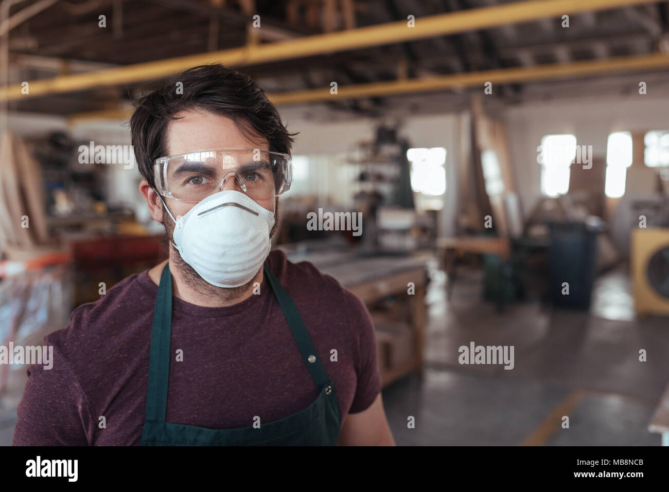 Young woodworker wearing protective gear in his workshop - Stock Image