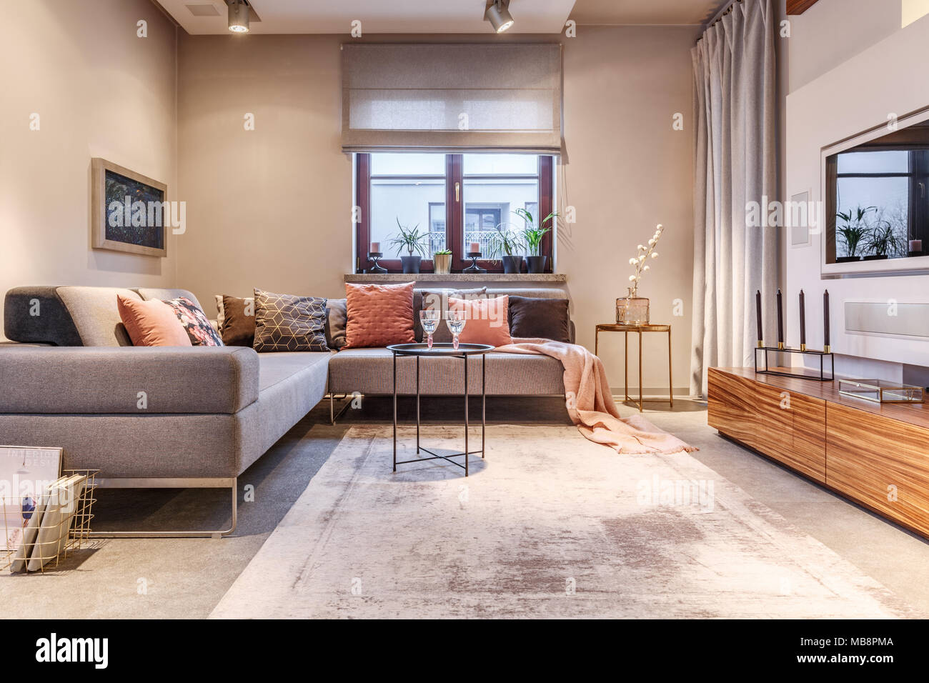 Cozy living room interior with a big sofa many cushions wooden shelves curtains mirror and ornaments & Cozy living room interior with a big sofa many cushions wooden ...