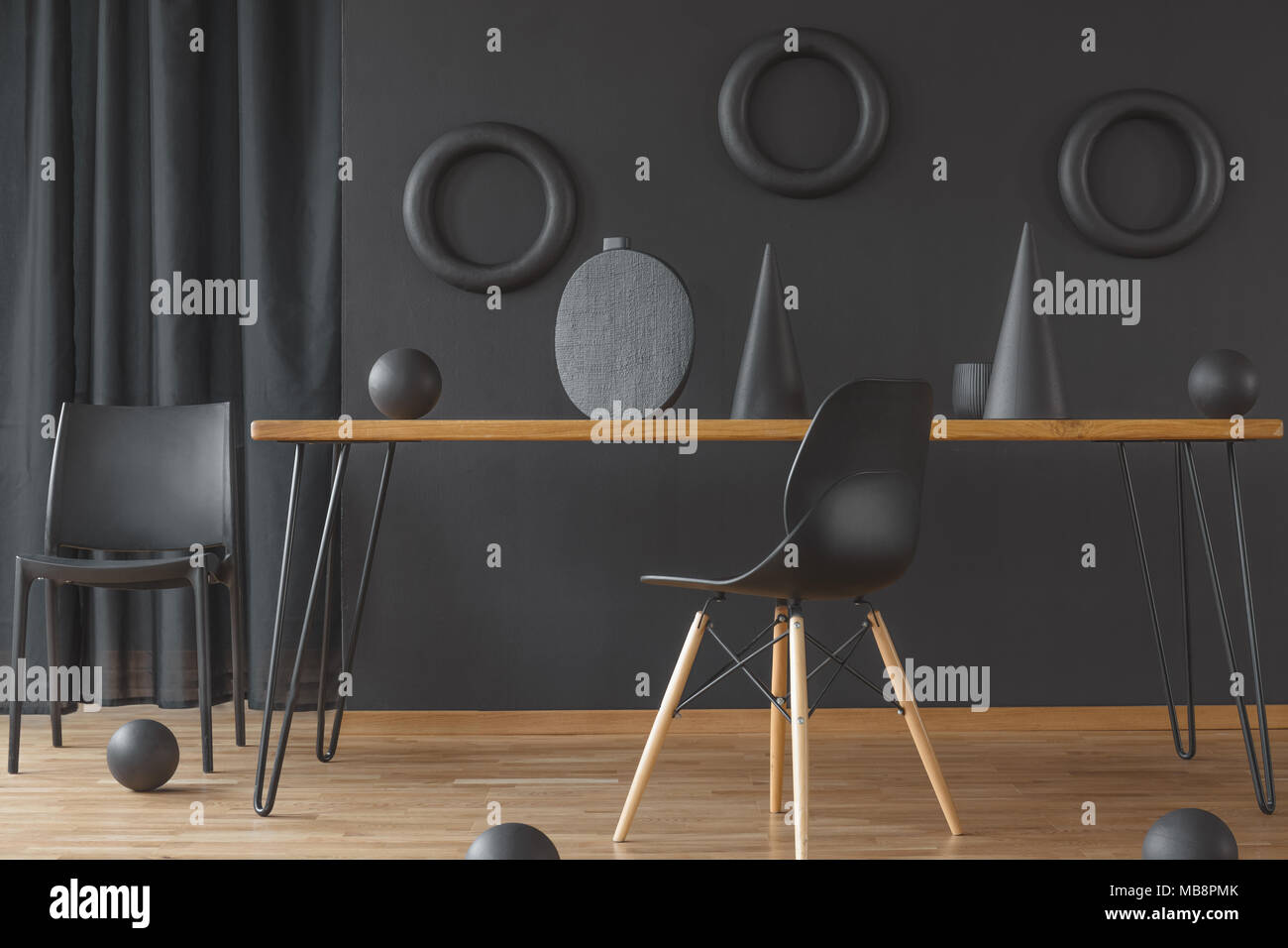 Black and wood dining room interior with hairpin table, two chairs and handmade sculptures - Stock Image