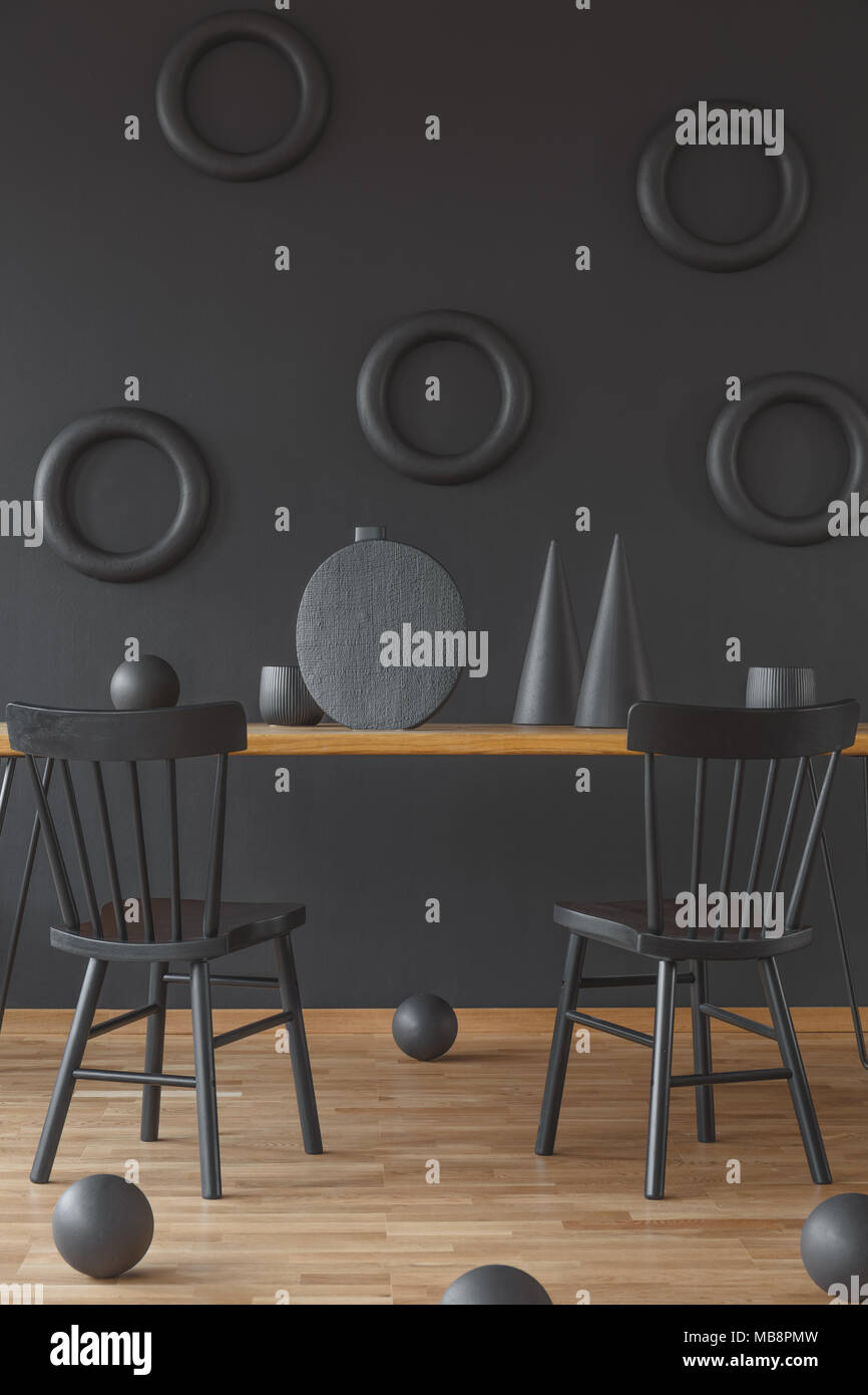 Wooden sculptures in round and cone shapes placed on the floor and table in black dining room interior with two chairs - Stock Image