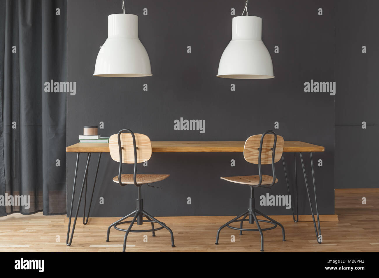 Two white lamps hanging above hairpin table in black dining room interior with curtain and chairs - Stock Image