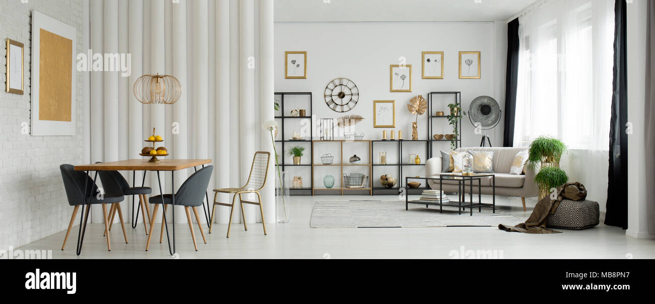 Gold Painting On A White Brick Wall In Open Space Living Room Interior With A Wooden Dining Table And Beige Couch Stock Photo Alamy