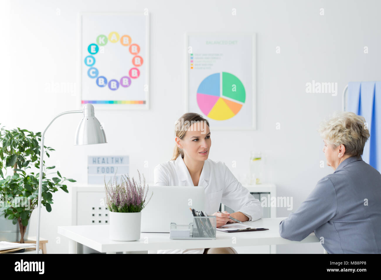 Elderly woman talking to a female doctor at a diet consultation in a bright office - Stock Image
