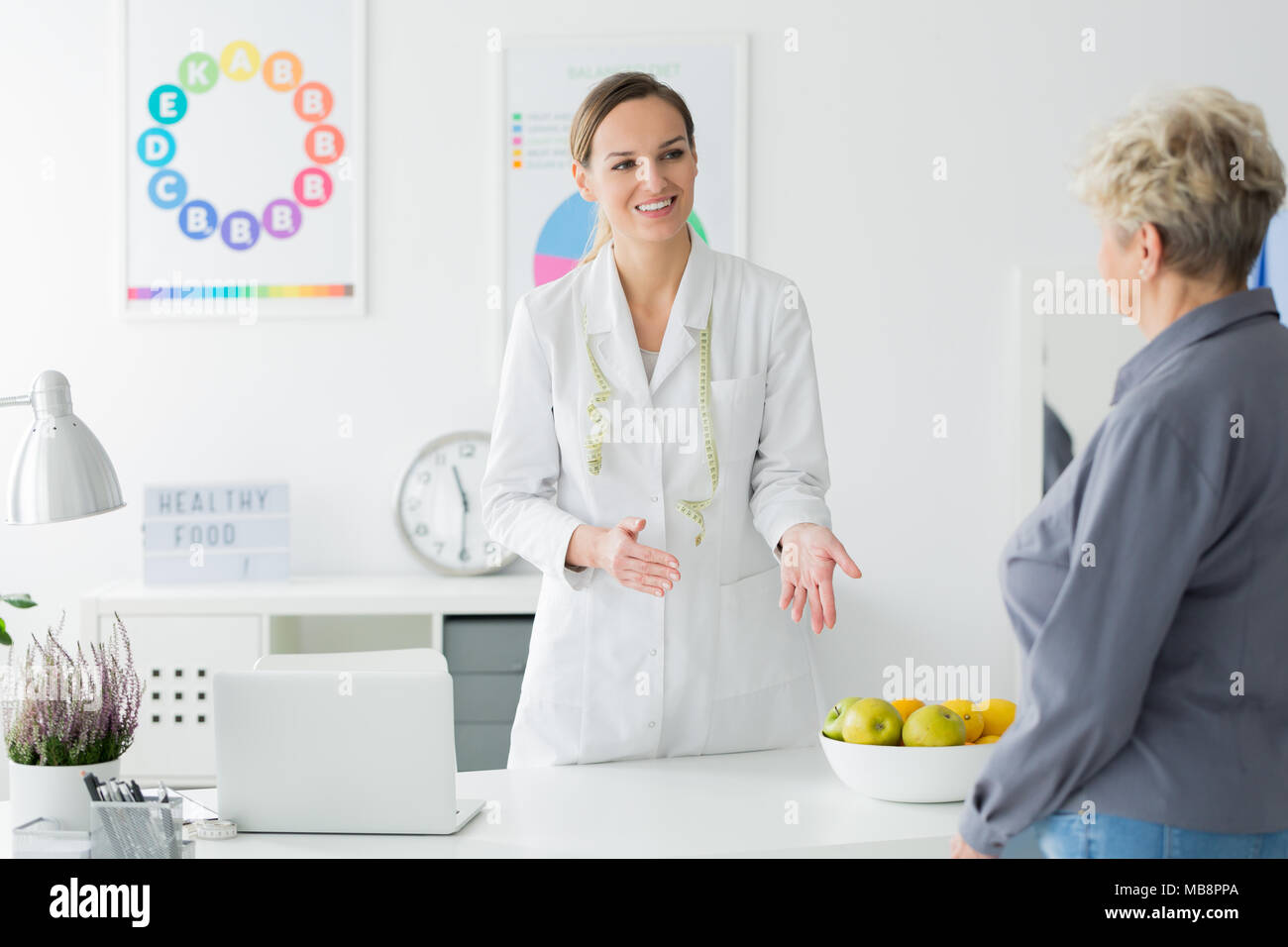 Dietician with measuring tape welcoming her elderly client at an appointment to plan weight loss - Stock Image