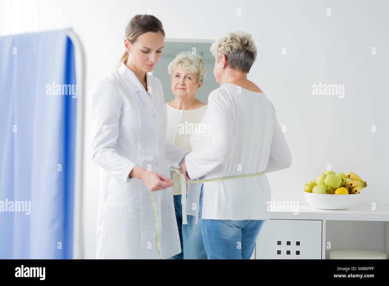 Young dietician taking waist measurements of her senior patient during appointment at a bright office - Stock Image