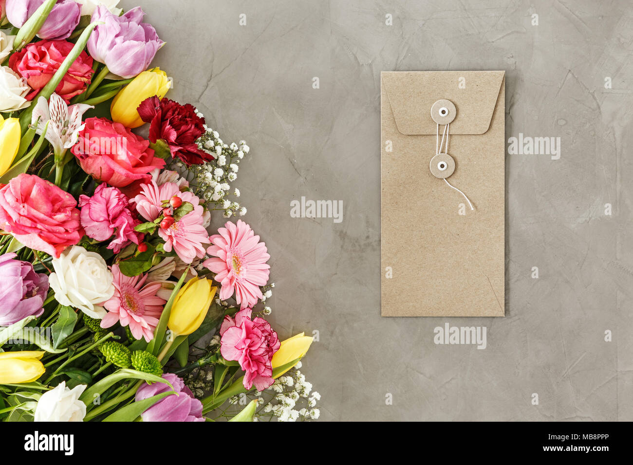 Brown envelope for a greeting card lying on a gray table next to a brown envelope for a greeting card lying on a gray table next to a bouquet of flowers for mothers day izmirmasajfo Gallery