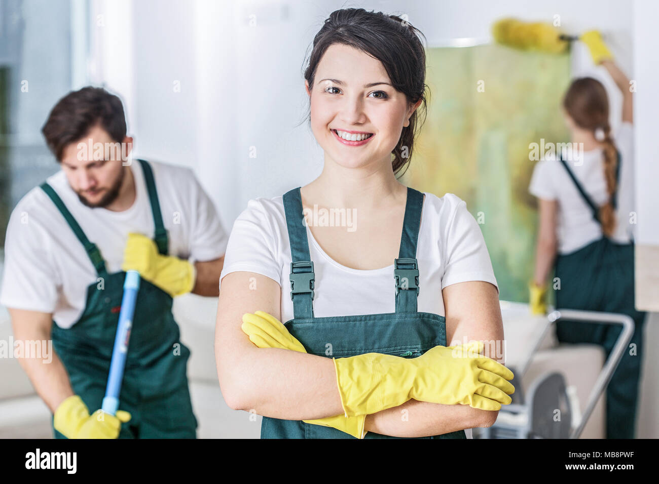 Smiling cleaning lady in a green uniform and yellow rubber gloves at work - Stock Image