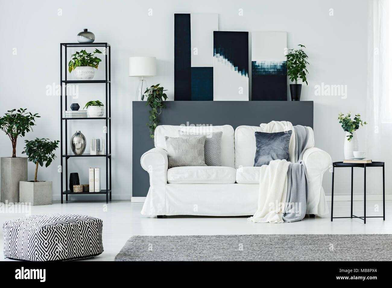 Comfortable sofa by a gray wall with abstract paintings in a ...