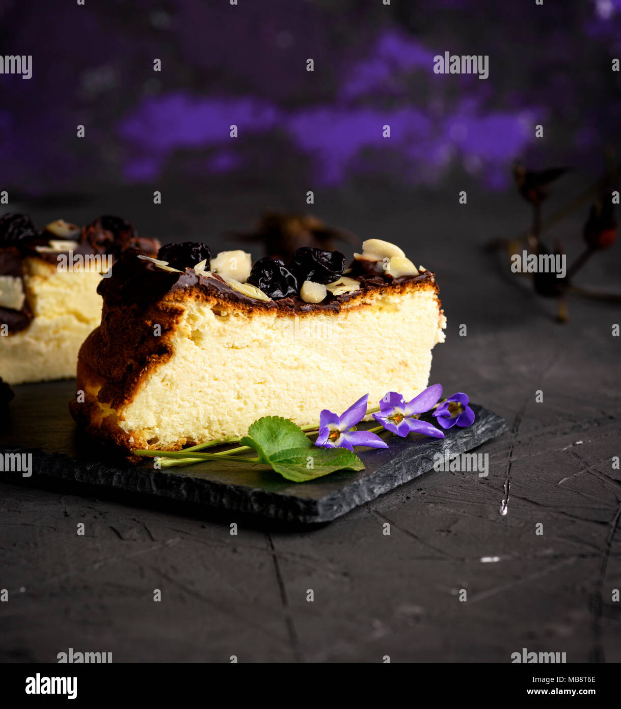 a piece of cheesecake on a black background sprinkled with almond shavings and dry cherries, close up - Stock Image