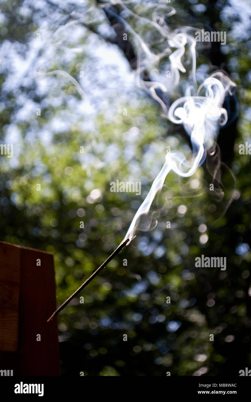Waft of smoke rising from a stick of incense - Stock Image