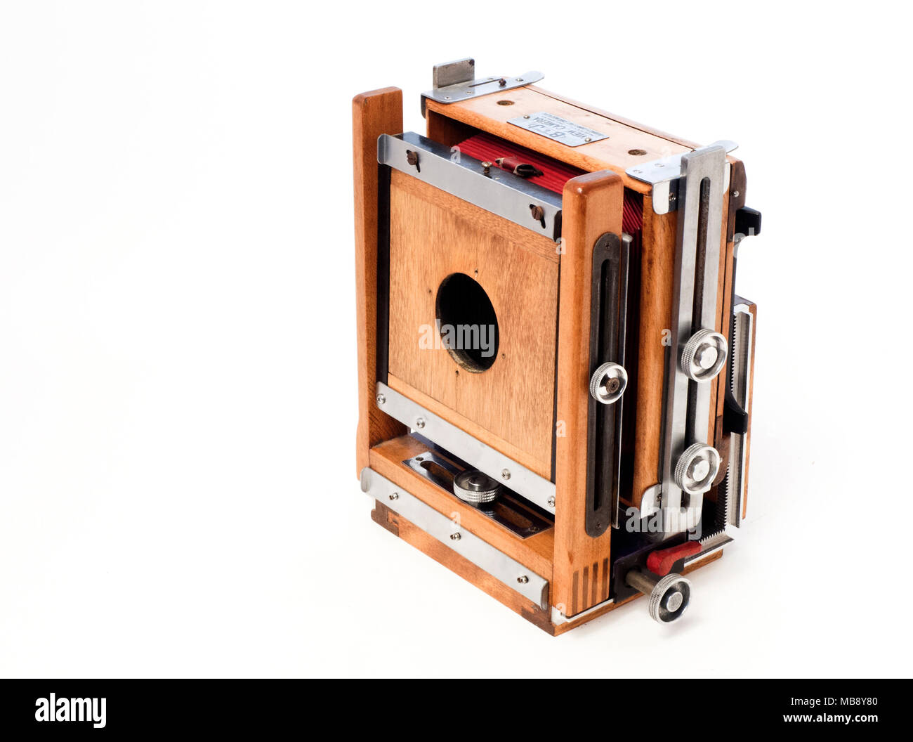 A folded Burke & James 4x5 format flatbed view camera with red bellows. - Stock Image