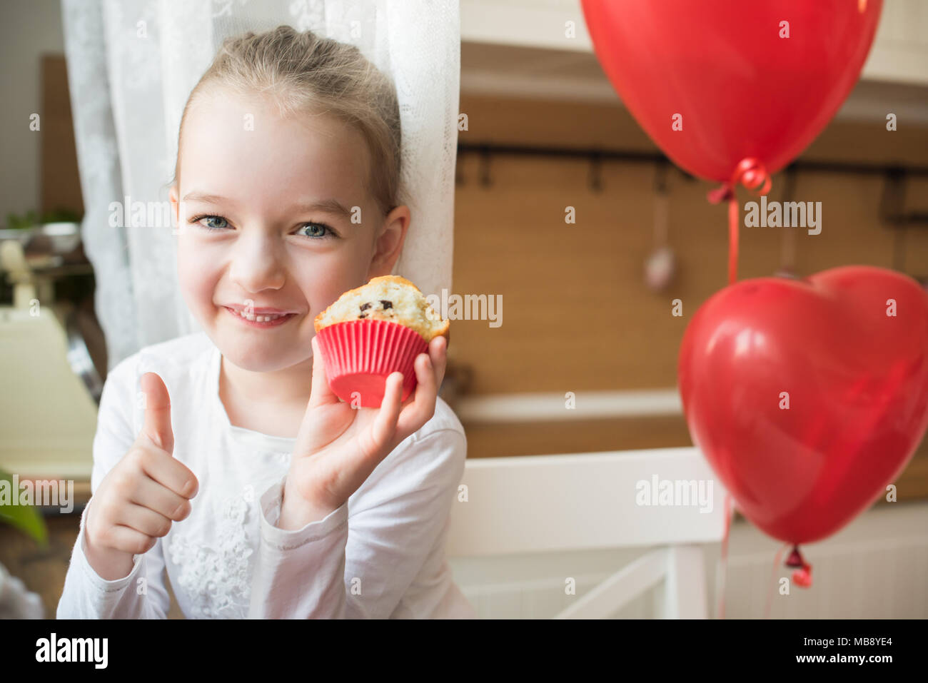 Cute preschooler girl celebrating 6th birthday. Girl eating her birthday cupcake in the kitchen, surrounded by balloons, showing thumbs up. - Stock Image