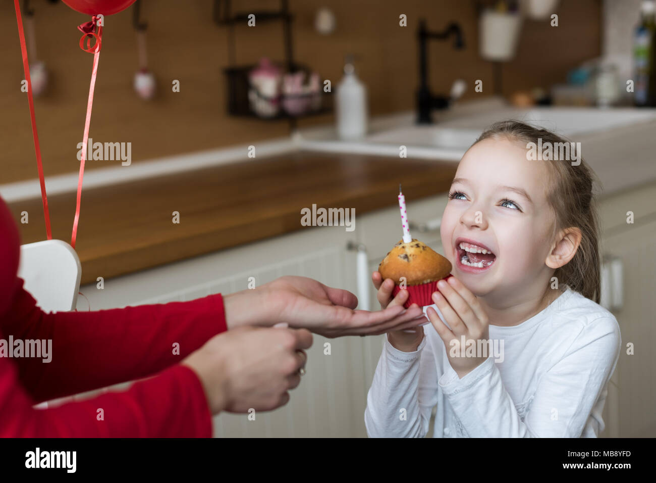 Cute preschooler girl celebrating 6th birthday. Mother giving daughter birthday cupcake with a candle. Childrens birthday party concept. - Stock Image
