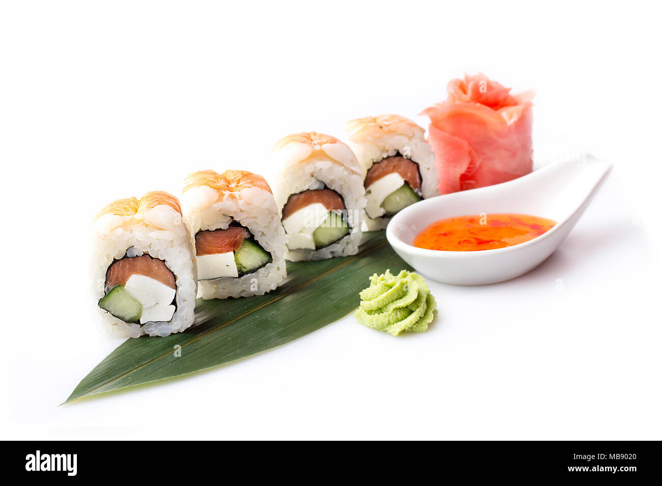 A fresh appetizing set of sushi rolls with shrimp laid out on a banana leaf. Stock Photo