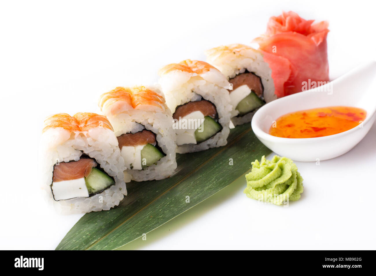A set of sushi rolls with shrimp and cream cheese laid out on a banana leaf with a spicy sauce. Stock Photo
