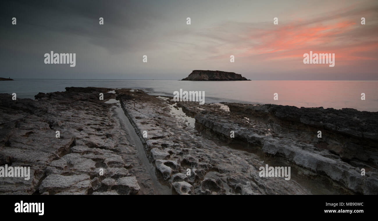 Rocky Seascape at dramatic sunset with the small  island of Geronisos st.  Georges cape at Paphos area Akamas peninsula in Cyprus - Stock Image